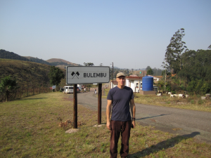 John beside Bulembu town sign