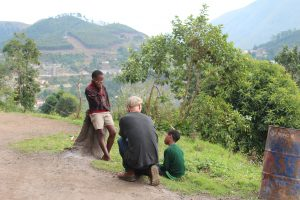 John chatting with kids on hillside